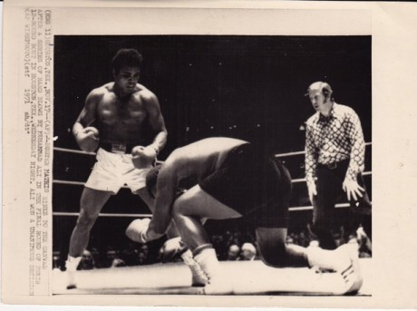 ALI SENDS BUSTER TO THE CANVAS WIRE PHOTO